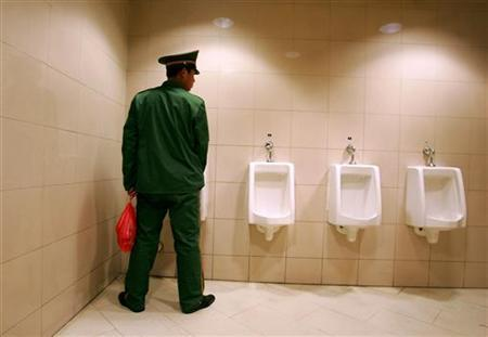 A man uses a public toilet in Beijing, November 17, 2004. Food stalls attached to Beijing's public toilets will be removed in good time for next year's Olympics, state media said Saturday. REUTERS/Claro Cortes IV