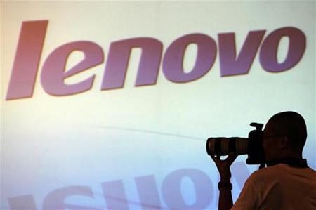 A photographer takes photos in front of a screen during a Lenovo Group Ltd. news conference in Hong Kong May 23, 2007. Lenovo Group Ltd., the world's third-largest maker of personal computers, is battling with its Taiwan rival Acer Inc. to buy European PC maker Packard Bell BV, a Hong Kong newspaper reported on Tuesday. REUTERS/Paul Yeung