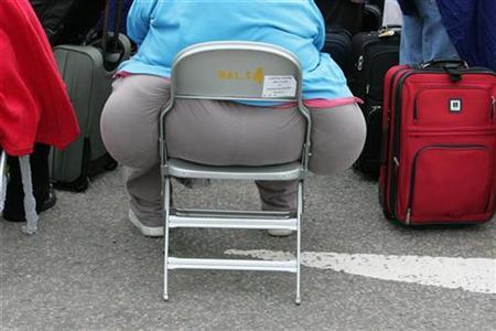 A passenger waits for a delayed flight at Heathrow airport's terminal four in London, August 12, 2006. Carrying a spare tire or two around the waist has become socially acceptable in the United States as the population's waistlines have expanded, according to a study released on Tuesday. REUTERS/Toby Melville