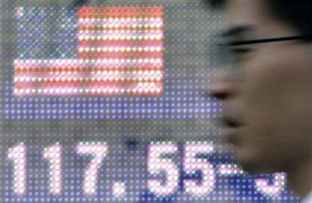 A man passes an electronic board displaying the dollar rate against the yen in Tokyo August 6, 2007. REUTERS/Yuriko Nakao