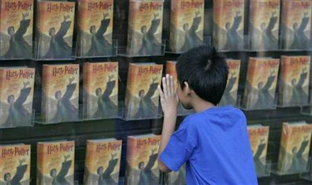 A Harry Potter fan looks at a window display of J.K. Rowling's ''Harry Potter and the Deathly Hallows'' while awaiting its release at a bookstore in Manila July 21, 2007. Police have arrested a high school student suspected of posting his own translation of the latest Harry Potter book on the Internet weeks ahead of the official French release date, a newspaper reported on Wednesday. REUTERS/Cheryl Ravelo