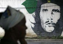 <p>Um mulher próxima a mural com a imagem de Ernesto 'Che' Guevara, em Havana. Passados 40 anos da morte do guerrilheiro, a imagem dele continua sendo o souvenir preferido dos turistas que visitam Cuba. Photo by Enrique De La Osa</p>