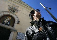 <p>O padre Antoniu Petrescu canta em frente à igreja na vila de Sorbo, Itália. O padre acredita que você pode venerar Deus e Elvis Presley ao mesmo tempo. Como padre católico e sósia de Elvis, ele encontra sua inspiração espiritual no velho ídolo do rock. Photo by Dario Pignatelli</p>