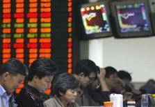 <p>Pessoas checam informações em bolsa de Nanjing, dia 15 de outubro. As bolsas de valores da Ásia fecharam a quinta-feira em alta. Photo by Sean Yong</p>
