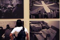 <p>Jornalista olha fotografias em exposição sobre o conflito no País Basco, em Bilbao, dia 16 de outubro. As fotografias causaram apelos dramáticos para que seja cancelada a exibição do Museu Guggenheim de Bilbao. Photo by Vincent West</p>