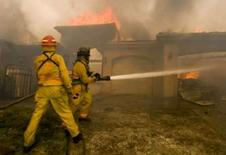 <p>Bombeiros tentam combater o fogo em uma casa que foi incendiada em Poway, na Califórnia. O presidente norte-americano, George W. Bush, autorizou nesta tera-feira que as agncias federais coordenem trabalhos de socorro nas reas afetadas por incndios no sul da Califrnia. Bush declarou que a regio enfrenta um estado de emergncia. Photo by Fred Greaves</p>