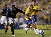 <p>Atacante Robinho se livrea do equatoriano Jacinto Spinoza durante partida entre as equipes pelas eliminatórias da Copa do Mundo de 2010, no Maracanã, na semana passada. Photo by Bruno Domingos</p>
