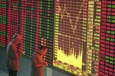 <p>Pessoas checam informações em painel eletrônico em Wuhan, China central. A maior parte das bolsas de valores da Ásia fechou em alta nesta quinta-feira, impulsionadas por expectativas de corte de juro nos Estados Unidos. Photo by China Daily</p>