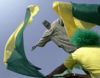 <p>Torcedor sacode bandeira em frente ao Cristo Redentor, no Rio de Janeiro. Grande parte dos 'boleiros' está em festa com a confirmação do Brasil como sede da Copa do Mundo de 2014, enquanto os críticos alertam para a falta de transparência e a eventual corrupção na gestão dos recursos para preparar o grande evento. Photo by Bruno Domingos</p>