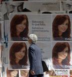 <p>Homem passa por pôster de Cristina Kirchner em Buenos Aires, 26 de outubro. A presidente eleita da Argentina, Cristina Fernández de Kirchner, começou na terça-feira a trabalhar na transição de governo, e já avalia aumentar os impostos sobre as exportações de grãos. Photo by Marcos Brindicci</p>