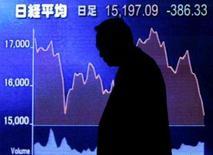 <p>A silhueta de um homem contra um quadro com cotação de ações, em Tóquio. As bolsas de valores da Ásia fecharam a segunda-feira em queda influenciadas por preocupações com mais perdas de instituições financeiras com crédito e uma queda acentuada nos preços do petróleo. Photo by Toru Hanai</p>