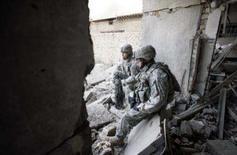 <p>Soldados norte-americanos descansam após vasculhar casa durante patrulha em Bagdá. A Câmara dos Deputados norte-americana, liderada pelo Partido Democrata, aprovou na noite de quarta-feira um cronograma de retirada das tropas no Iraque, desafiando o presidente George W. Bush ao atrelar a medida à liberação de 50 bilhões de dólares para gastos com a guerra. Photo by Stefano Rellandini</p>