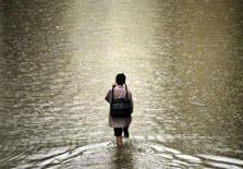 <p>Homem caminha por estrada inundada em Mumbai no dia 3 de agosto. Os delegados que discutem causas e efeitos das mudanças climáticas globais em evento da ONU ainda parecem distantes de um acordo, disseram fontes ligadas às negociações na quinta-feira. Photo by Punit Paranjpe</p>