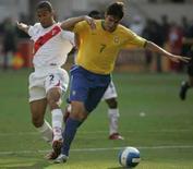 <p>Peruano Alberto Rodriguez (esquerda) tenta roubar a bola de Kaká durante partida das eliminatórias da Copa do Mundo de 2010, em Lima, neste domingo. Photo by Enrique Castro-Mendivil</p>