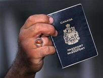<p>File photo of a man holding his Canadian passport. Canada's passport office has fixed a security flaw in its Web site which allowed computer users to access the personal data of passport applicants, officials said on Tuesday. REUTERS/Fatih Saribas</p>
