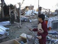 <p>Мальчик смотрит на руины домов, разрушенных взрыв экстремиста-смертника в городе Байджи, Ирак 8 декабря 2007 года. По меньшей мере 16 человек погибли и 27 получили ранения в результате взрыва смертницы в городе Эль-Микдадия в 90 километрах к северо-востоку от Багдада, сообщила полиция Ирака. (REUTERS/Sabah al-Bazee)</p>