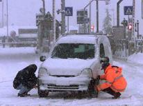 <p>Due persone montano le catene da neve ad un'auto in autostrada. Foto d'archivio. PH/WS</p>