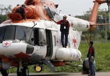 <p>Tripulação prepara helicóptero venezuelano MI-17, marcado com símbolo da Cruz Vermelha, que continua parado em aeroporto de Villavicencio, Colômbia, 29 de dezembro, à espera de coordenadas do local de entrega de reféns das Farc. Photo by Jose Miguel Gomez</p>