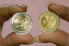 <p>Una donna mostra i due volti di una moneta da due euro a Malta, che assieme a Cipro oggi ha adottato l'euro. REUTERS/Darrin Zammit Lupi</p>