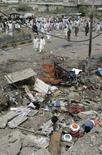 """<p>Люди на месте подрыва взрывного устройства в городе Карачи, Пакистан, 19 июля 2007 года. Американский участник группировки """"аль-Каида"""" Адам Гадан призвал всех боевиков-исламистов встретить президента США Джорджа Буша взрывами бомб. (REUTERS/Athar Hussain)</p>"""