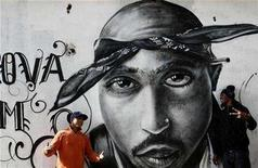 """<p>Two young talk next to a graffiti of murdered rapper Tupac Shakur in the Cova da Moura district in Lisbon December 6, 2007. """"Somebody Scream! Rap Music's Rise to Prominence in the Aftershock of Black Power"""" is the story of this powerfully influential and yet surprisingly little-understood American musical genre. REUTERS/Nacho Doce</p>"""