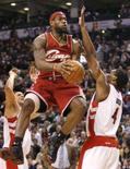 <p>O ala do Cleveland Cavaliers LeBron James (centro) tenta marcar contra o Toronto Raptors Anthony Parker, durante partida pela temporada regular da NBA no domingo, em Toronto. LeBron marcou 24 de seus 39 pontos no último quarto da partida que levou o Cleveland à vitória de virada, por 93 a 90, sobre o Raptors. Photo by Mike Cassese</p>