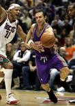 <p>O armador do Phoenix Suns Steve Nash (13)  passa pela defesa do Milwaukee Bucks durante partida pela NBA. Steve Nash ajudou o Phoenix Suns a reverter uma desvantagem de nove pontos no último período para derrotar o Milwaukee Bucks por 114 a 105, de virada, na noite de terça-feira. Photo by Allen Fredrickson</p>