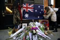 <p>(L-R) Libby Hobday, 28, of Melbourne, Australia, and Christina Jeffs, 22, of Los Angeles, California, tape an Australian flag above a makeshift memorial in front of the building where actor Heath Ledger died in New York January 23, 2008. REUTERS/Nicholas Roberts</p>