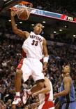 <p>O ala do Toronto Raptors Jamario Moon (esq) enterra bola durante partida contra o  Washington Wizards pela temporada regular da NBA.O Toronto Raptors atropelou o Washington Wizards por 122 a 83, na quarta-feira, igualando o recorde de maior vitória da equipe na história. Photo by Mike Cassese</p>