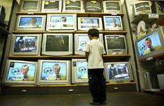 <p>Un abambino davanti alla vetrina di un negozio piena di apparecchi televisivi in funzione. REUTERS/Dylan Martinez DJM</p>
