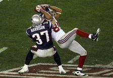 <p>New York Giants receiver David Tyree (R) hauls in a Eli Manning (not pictured) pass as New England Patriots safety Rodney Harrison (37) defends in the fourth quarter for a first down during Super Bowl XLII in Glendale, Arizona February 3, 2008. REUTERS/Jeff Topping</p>