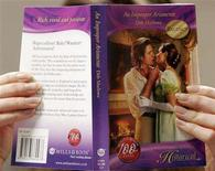 <p>A woman poses for the camera with a Mills & Boon novel, in London February 7, 2008. REUTERS/John Voos</p>