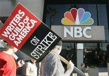 "<p>Members of the Writers Guild of America carry signs on the picket line at NBC studios in Burbank, California February 8, 2008. The union representing Hollywood's striking writers said it reached a ""tentative deal"" with studios and will meet members later on Saturday to discuss ending a three-month walkout that has crippled television production and overshadowed the awards season. REUTERS/Fred Prouser</p>"