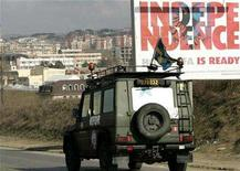 <p>A vehicle of NATO's Kosovo peace force, with a Swedish flag, drives past a billboard advertising a new hotel with the banner 'INDEPENDENCE' in the capital, Pristina, February 6, 2008. The European Union is set to complete authorization of a big supervisory mission in Kosovo this week, just before the territory is expected to declare independence from Serbia, diplomats and EU officials said. REUTERS/Hazir Reka</p>