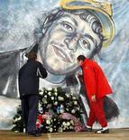 <p>Due giocatori dell'Olympiakos depongono fiori davanti ad un disegno di Gabriele Sandri, il tifoso della Lazio ucciso da un poliziotto l'11 novembre. REUTERS/Giampiero Sposito (ITALY)</p>