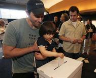 <p>Greg Fields, a member of The Writers Guild of America, lets his 3-year-old son Caelan drops his vote in the ballot box at Writers Guild Theater in Beverly Hills, California after voting in a special election February 12, 2008, with the expectation that a 14-week-old strike against major film and TV studios will be lifted. REUTERS/Rick Loomis/Pool</p>