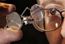 <p>A worker inspects a freshly pressed Canadian one dollar coin at the Royal Canadian Mint in Winnipeg on November 14, 2007. REUTERS/Fred Greenslade</p>