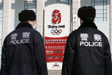 <p>Two Chinese police officers keep watch near the Beijing Olympic countdown clock near Tiananmen Square in Beijing, February 13, 2008. REUTERS/Claro Cortes IV</p>
