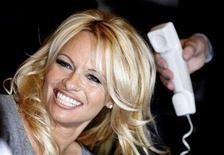 <p>Actress Pamela Anderson smiles as she talks on the phone with France's Actress Brigitte Bardot (not pictured) during a visit to Bardot's foundation for animals rights in Paris February 14, 2008. REUTERS/Charles Platiau</p>