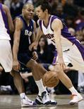 <p>Steve Nash do Phoenix Suns (dir) passa por Devean George do Dallas Mavericks durante partida pela temporada regular da NBA. O brasileiro Leandrinho marcou 26 pontos e foi, junto com Amare Stoudemire, o grande destaque na vitória do Phoenix Suns sobre o Dallas Mavericks, por 109-97, na quinta-feira, pela NBA. Photo by Jeff Topping</p>