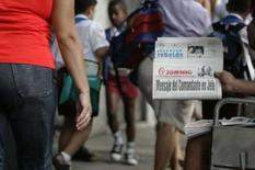 <p>Vendedor de jornal mostra a edição do Granma que traz a carta de renúncia do comandante Fidel Castro, nesta terça-feira, em Havana. Photo by Enrique De La Osa  REUTERS/Enrique De La Osa</p>