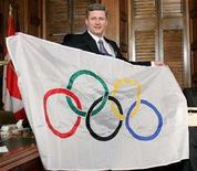 <p>Canadian Prime Minister Stephen Harper holds an Olympic flag upside-down after it was presented to him by Vancouver Mayor Sam Sullivan in his office on Parliament Hill in Ottawa, April 26, 2006. The Canadian government pledged an additional C$20 million ($19.7 million) to the 2010 Winter Olympics on Friday, picking up half the expected tab for the Vancouver Games' opening and closing ceremonies. REUTERS/Chris Wattie</p>