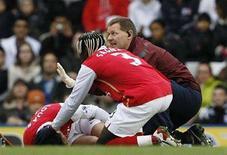 <p>Il calciatore dell'Arsenal Eduardo Da Silva a terra dopo la frattura a una gamba in seguito a un fallo subìto. REUTERS/Darren Staples</p>