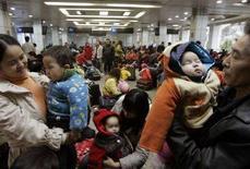 <p>Coppie cinesi con in braccio i loro bambini. REUTERS/Bobby Yip (CHINA)</p>