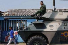 <p>Soldado venezuelano descansa sobre veículo de transporte blindado que se dirigia para a fronteira com a Colômbia. A Venezuela enviou tanques e unidades da Aeronáutica e da Marinha para a fronteira com a Colômbia, em sua primeira mobilização militar de peso. Photo by Stringer</p>