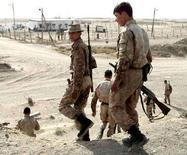 <p>Узбекские солдаты охраняют дорогу неподалеку от города Термез. 16 октября 2001 года. Узбекистан разрешил американским военным использовать авиабазу Термез на юге страны для операций в соседнем Афганистане в составе международного контингента НАТО, сообщили в четверг представитель НАТО и посольство США в Узбекистане. (REUTERS/Alexander Demianchuk)</p>