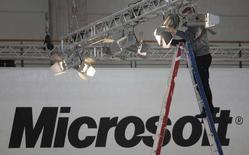 <p>Un lavoratore allestisce uno stand Microsoft in una fiera. REUTERS/Hannibal Hanschke (GERMANY)</p>