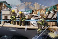 <p>Firefighters work at the scene, where the roof of a bakery warehouse collapsed, in Morin Heights, Quebec March 12, 2008. REUTERS/Shaun Best</p>
