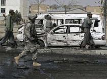 <p>Soldado norte-americano caminha por veículos danificados em Cabul. Um ataque suicida com carro-bomba matou oito civis afegãos em um ataque contra tropas dos Estados Unidos no aeroporto da capital do Afeganistão na quinta-feira, disse um porta-voz da Otan. Photo by Stringer</p>