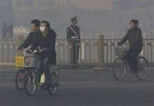 <p>Una donna in bicicletta con la mascherina anti-smog nella centrale piazza Tienanmen a Pechino. REUTERS/David Gray</p>